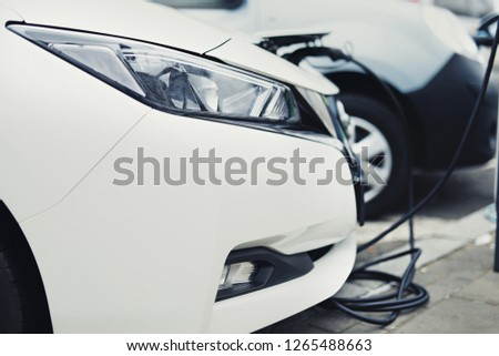 Electric car charging station. Close up of the power supply plugged into an electric car being charged. - Image #1265488663