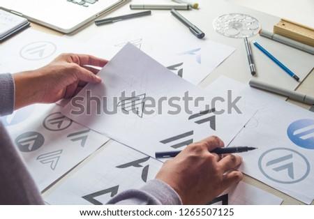Graphic designer drawing sketch design creative Ideas draft Logo product trademark label brand artwork. Graphic designer studio Concept. #1265507125