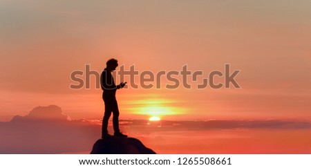 Happy and successful lover at sea sunset. Silhouette of a male freelancer, standing on top of mountain with smartphone.  Royalty-Free Stock Photo #1265508661