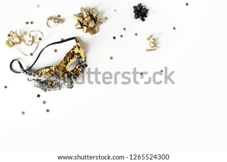 New Year festive composition with carnival mask, black and gold confetti stars and ribbons. Party decoration, celebration concept. Flat lay, top view. Empty space. #1265524300