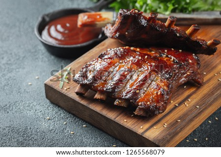 Closeup of pork ribs grilled with BBQ sauce and caramelized in honey. Tasty snack to beer on a wooden Board for filing on dark concrete background #1265568079
