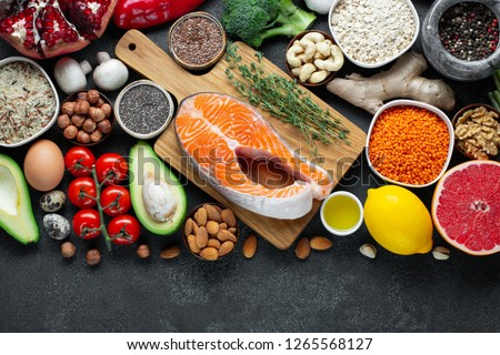 Healthy food clean eating selection: fish, fruit, nuts, vegetable, seeds, superfood, cereals, leaf vegetable on black concrete background. Flat lay #1265568127