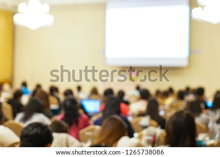 Blurred group of people sitting in seminar conference room with white screen #1265738086