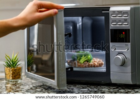 Using the microwave oven to heat food. Heating plastic container with broccoli and buckwheat in the microwave #1265749060