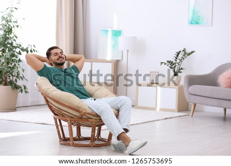 Handsome young man sitting in armchair at home. Space for text #1265753695