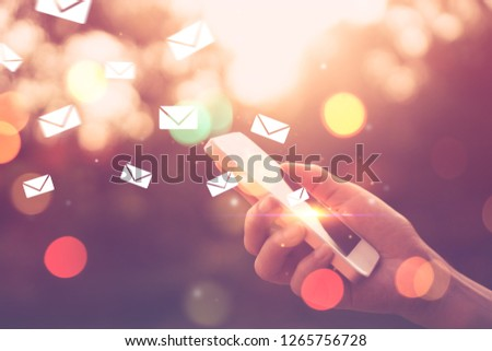 Woman hand using smart phone at outdoor nature park with sunset sky and email drawing flying abstract background. Copy space technology business and travel nature holiday concept. Vintage tone color. #1265756728
