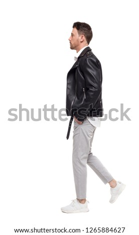 Side view of going  handsome man in a leather jacket and trousers. walking young guy . people collection.  backside view of person.  Isolated over white background. The rocker goes past the frame #1265884627