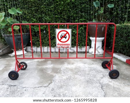 Movable traffic barrier with no parking sign and four wheels.It is on concrete floor in front of plant wall.Security concept. #1265995828