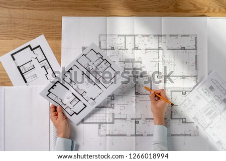 High angle above top view cropped photo clever intelligent success lady in her formal wear shirt she sit at the desk in bright loft interior hold graphs in hands read technical property information #1266018994
