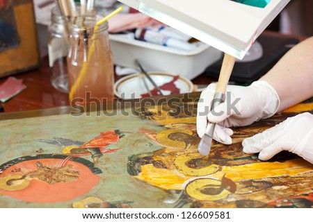 Restorer gilding on the Christian icon with agate burnisher at restoration workshop