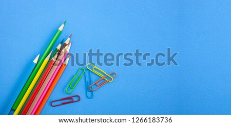 Back to school concepts banner template design, Colorful crayon pencils and clips for art and drawing on vibrant blue background with copy space. View from above, Closeup.