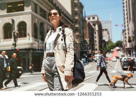 confident asian business woman in sunglasses standing on zebra crossing enjoy sunshine looking to blue sky. people walking dog and businessman in background. busy street road city urban san francisco #1266351253