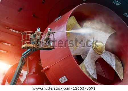 Worker on cherry picker car with safety harness in dry dock ship cleaning by water jet cleaners and Sand blasting during routine overhaul on outdated manual technology in shipyard #1266378691