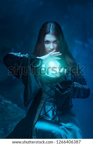 The witch with magic ball in her hands causes a spirits in cave Royalty-Free Stock Photo #1266406387
