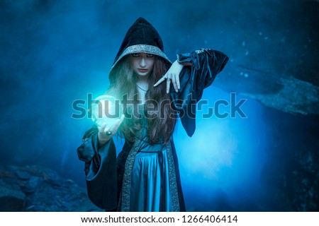 The witch with magic ball in her hands causes a spirits in cave Royalty-Free Stock Photo #1266406414