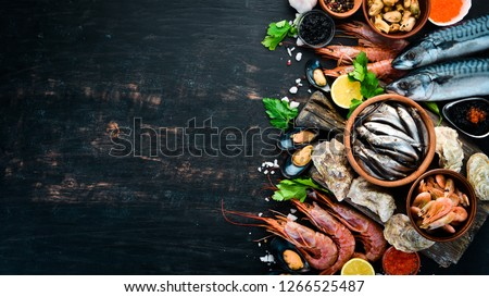 Seafood. Fresh fish, shrimp, oysters and caviar on a black wooden background. Top view. Free copy space. #1266525487