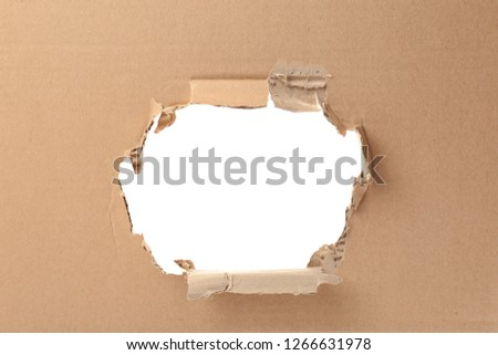 Hole in cardboard on white background. Recyclable material Royalty-Free Stock Photo #1266631978
