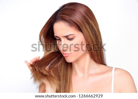 Beautiful woman looks stressed on her damaged hair #1266662929