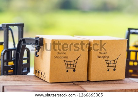 Cardboard boxes with shopping cart symbol on wooden block and mini crane truck nearby with natural background. Logistics and transportation management ideas and Industry business commercial concept. #1266665005