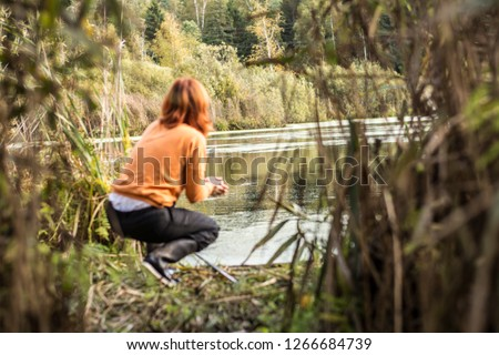 The girl is fishing. A woman is fishing. Hunting fish in swamp thickets with fishing rod. An inexperienced girl gets food in the wild. Fishing in the swamp. #1266684739