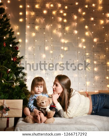 young mother and a little girl daughter are sitting at home on the sofa near the New Year tree. lights of garlands. comfort and warmth, homely atmosphere, preparing for the new year #1266717292