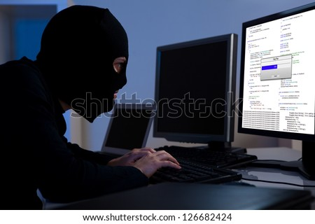 Masked hacker wearing a balaclava sitting at a desk downloading private information off a computer #126682424