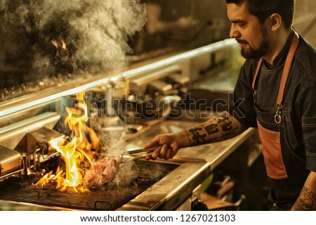 Side view of professional chef cooking delicious juicy beef steak on flaming grill. Handsome man with beard and tattoos on hand preparing food in modern restaurant kitchen.  #1267021303