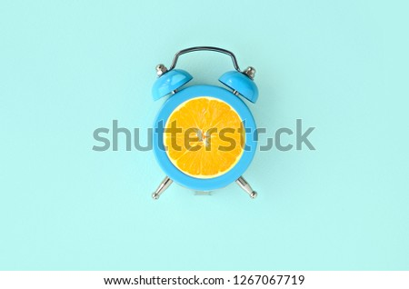 Fresh orange slice in small blue alarm clock #1267067719