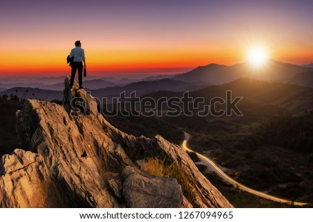 Concept vision, Young businessman wearing comfortable casual suit jacket standing holding business bag on top of peak mountain and looking forwards, success, competition and leader concept. #1267094965