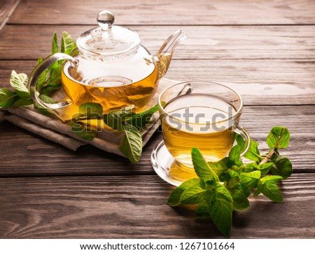 Fragrant fresh herbal tea of mint and melissa in a glass cup and a teapot on a dark wooden background. Traditional herbal drink. Place for text or design. #1267101664