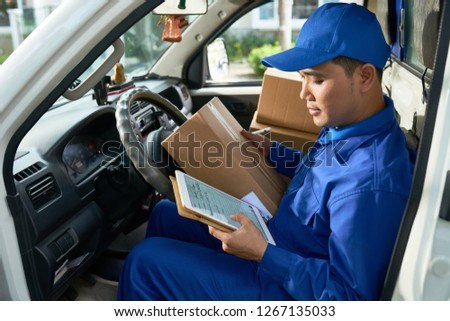 Courier checking address before delivery parcel to customer #1267135033