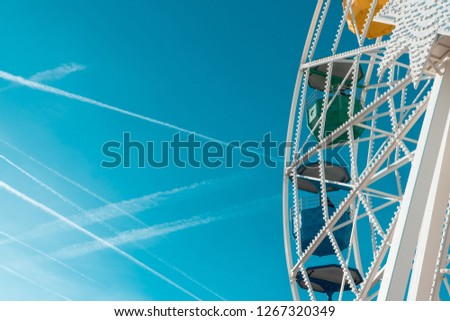 Colorful ferris wheel at fun amusement park with clear blue skies. #1267320349