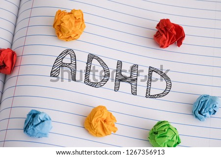 ADHD. Abbreviation ADHD on notebook sheet with some colorful crumpled paper balls on it. Close up. ADHD is Attention deficit hyperactivity disorder. #1267356913
