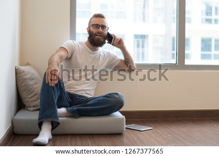 Content confident young man with beard having phone conversation. Handsome guy in glasses sitting on pillow at home. Communication concept #1267377565