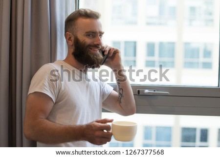 Cheerful excited man talking on phone while drinking coffee at home. Smiling handsome young bearded guy with tattoo standing at window. Communication concept #1267377568