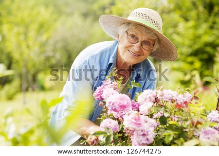 Senior woman with flowers in garden #126744275