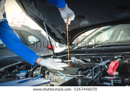 Mechanic repairing car with open hood,Side view of mechanic checking level motor oil in a car with open hood  #1267446070