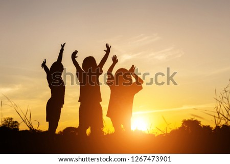 Silhouette of three little girls are having fun during sunset. #1267473901