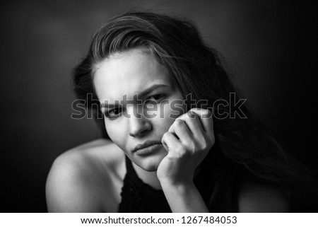 Dramatic black and white portrait of a beautiful girl on a dark background #1267484053