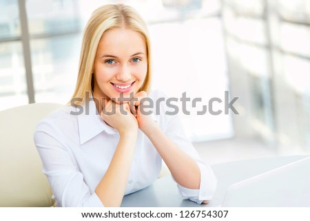 A portrait of a young business woman in an office #126754307