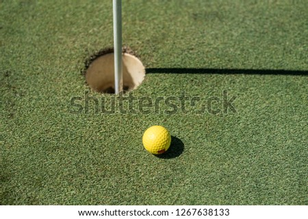 Golf field with yellow ball near the hole #1267638133