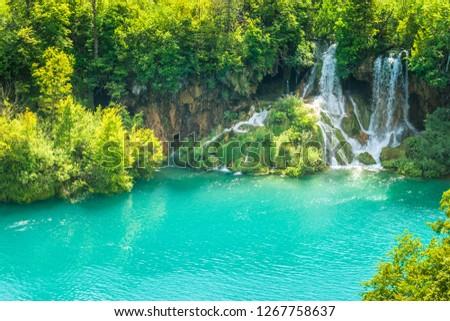 Waterfall at a turquoise lake. The Plitvice Lakes National Park, Croatia, Europe. #1267758637