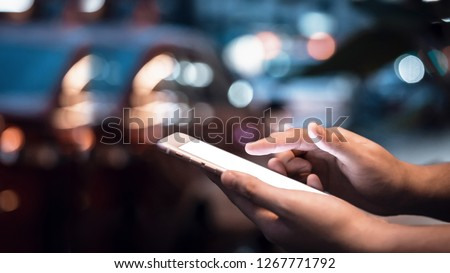 Close-up image of male hands using smartphone at night on city shopping street, searching or social networks concept, hipster man typing an sms message to his friends #1267771792