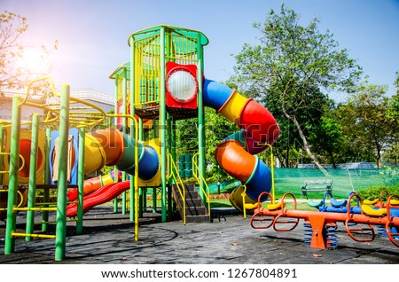 Colorful children playground,exercise kid,activities in outdoor public park surrounded by green trees at sunlight morning.Children run, slide,seesaw on modern playground.Funny toy land for child #1267804891