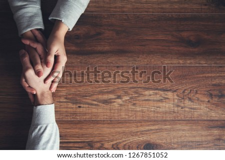 young couple hand on wooden table #1267851052