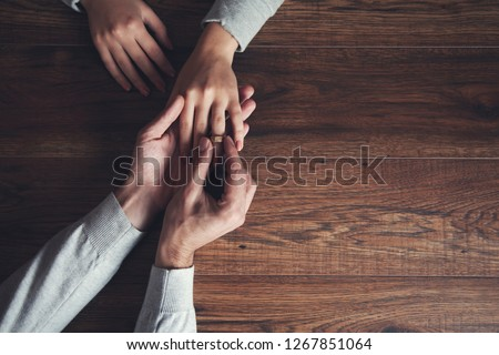 man with woman hand ring on wooden table #1267851064