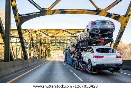 To meet the people need for passenger cars special big rig semi trucks are adapted to transport vehicles using mainly two-tiered semi trailers and transporting vehicles all around America and Canada #1267858423