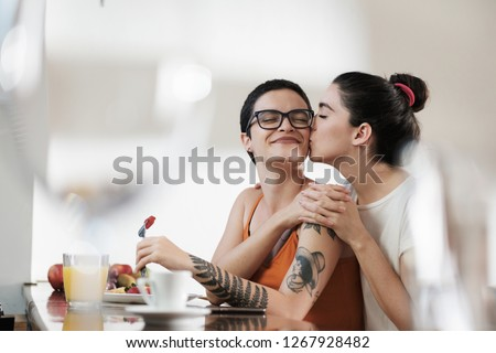 A couple of gay woman having breakfast together and holding hands while smiling and kissing. Same sex young married female couple in their daily routine at a morning showing some affection LGBT #1267928482