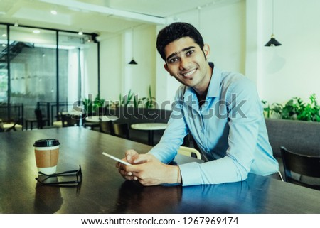 Portrait of happy young Indian businessman sitting in cafe. Young man sitting at table, using mobile phone, looking at camera and smiling indoors. Coffee break or freelance working concept #1267969474