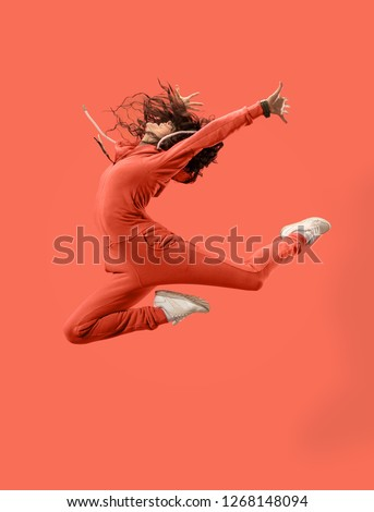 Freedom in moving. Mid-air shot of pretty happy young woman jumping and gesturing against coral studio background. Runnin girl in motion or movement. Human emotions and facial expressions concept Royalty-Free Stock Photo #1268148094